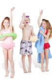 Trzy dziecka w plażowych kostiumach z plażowymi akcesoriami Zdjęcie Stock