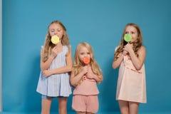 Trzy dziewczyn dziewczyna je cukierku lizaka siostry zdjęcia royalty free