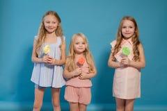 Trzy dziewczyn dziewczyna je cukierku lizaka siostry obrazy royalty free