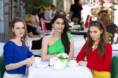 Trzy dziewczyn kobiety szczęśliwy obsiadanie przy stołem w lecie c Zdjęcia Royalty Free