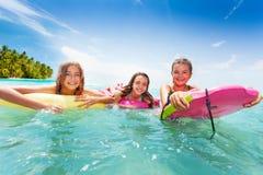 Trzy dziewczyn pływanie w morzu na surfboards Zdjęcia Royalty Free