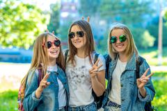 Trzy dziewczyn uczennicy nastolatek, będący ubranym cajgi odzieżowych i okulary przeciwsłonecznych Szczęśliwy ono uśmiecha się z  obrazy stock