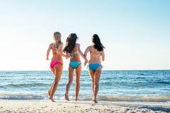 trzy dziewczyny ma zabawę na plaży Obrazy Stock
