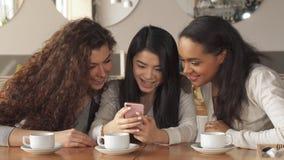 Trzy dziewczyny oglądają coś na smartphone przy kawiarnią zdjęcia stock