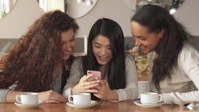 Trzy dziewczyny oglądają coś na smartphone przy kawiarnią zdjęcie wideo