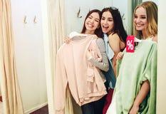 Trzy dziewczyny są trwanie w przebieralni i śmiać się Azjatycka kobieta trzyma różową bluzę sportowa i próbuje je na ona zdjęcie royalty free