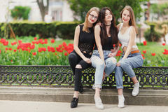 Trzy dziewczyny siedzą na parkowym tle obraz stock