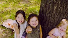 Trzy dziewczyny stoi blisko drzewa w parku i je pizzę zdjęcie wideo
