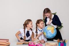 Trzy dziewczyny uczennicy na lekcji geografia z kulą ziemską w szkole zdjęcia stock