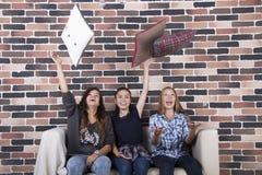 Trzy dziewczyny w domu bawją się miotanie poduszki up obraz royalty free