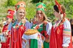Trzy dziewczyny w Rosyjskich ludowych kostiumach czekają gości z Zdjęcie Royalty Free