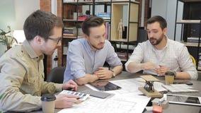 Trzy eksperta siedzi w biurze dyskutują biznesowych zagadnienia, używać pastylkę zbiory