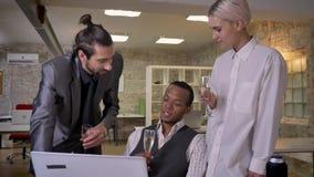Trzy etnicznego pracownika mówją opowieści, siedzący przy laptopem w biurze, pije szampana, komunikacyjny pojęcie zbiory wideo