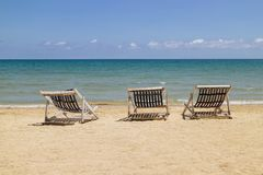 Trzy falcowania krzes?a na pla?y z dennym i jaskrawym niebem w tle przy Koh Mak w Trata, Tajlandia Sezonowy wakacje zdjęcie royalty free