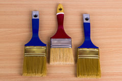 Trzy farby muśnięcie na stole Obraz Stock