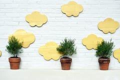 Trzy flowerpot z obłocznym drewnem na nowożytnym ściana z cegieł plecy obrazy royalty free