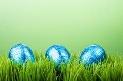 Trzy foliowego Wielkanocnego jajka na trawie Obrazy Royalty Free
