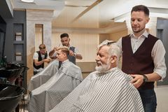 Trzy fryzjera męskiego ciie włosy klienci i przygotowywa zdjęcie royalty free
