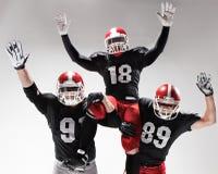 Trzy futbolu amerykańskiego gracza pozuje na białym tle Zdjęcie Stock