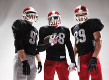 Trzy futbolu amerykańskiego gracza pozuje z piłką na białym tle Fotografia Stock