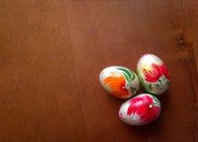 Trzy handmade drewnianego Easter jajka na drewnianym Odgórny widok fotografia stock