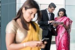 Trzy Indiańskiego ludzie biznesu używa nowożytnych przyrząda indoors obraz stock