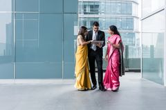Trzy Indiańskiego ludzie biznesu używa pastylka peceta indoors obraz royalty free