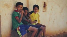 Trzy Indiańskiej chłopiec siedzi outdoors, je układy scalonych i patrzeje kamera, INDIA, NEPAL, KWIECIEŃ 2018 zbiory