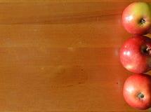 Trzy jabłka na desce Fotografia Stock