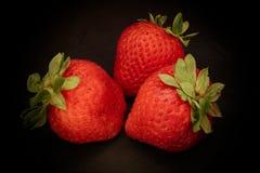 Trzy jagody truskawkowej na czarnym tle Obrazy Stock