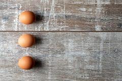 Trzy jajka w pionowo rzędzie z cieniami na drewnianym tle zdjęcie stock