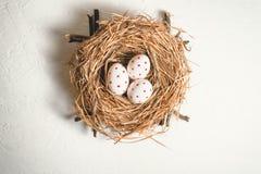 Trzy jajka z czerwonymi punktami w sianie gniazdują Wielkanocnego wakacje zdjęcia royalty free