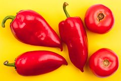 Trzy jaskrawego czerwonego pieprzu i dwa czerwonego pomidoru na żółtego tła odgórnym widoku zamykają w górę obraz stock