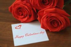 Trzy jaskrawej czerwonej róży i małego prześcieradło papier z inskrypcją! ` walentynek Szczęśliwy dzień! ` na drewnianym brown tł zdjęcia stock