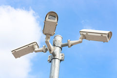 Trzy kamery bezpieczeństwa przeciw niebieskiemu niebu Obraz Royalty Free
