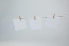 Trzy kleistej notatki wiesza na odzieżowej linii Zdjęcie Stock