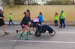 Trzy kobiet pchnięcia wózek inwalidzki więc niepełnosprawna osoba możemy uczestniczyć w St Patricks dniu Biegającym w Tulsa Oklah obraz royalty free