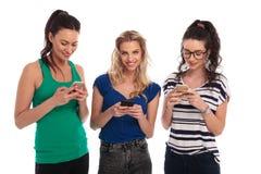 Trzy kobiet szczęśliwa przypadkowa gadka na ich telefonach Fotografia Stock