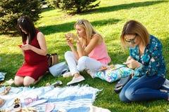 Trzy kobieta patrzeje w ich smartphones w lato zieleni parku fotografia stock
