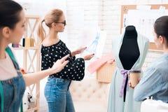 Trzy kobiety przy szaty fabryką Dyskutują projekt nowa suknia fotografia royalty free