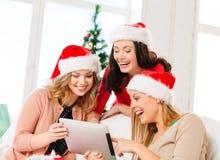Trzy kobiety w Santa pomagiera kapeluszach z pastylka komputerem osobistym Fotografia Stock