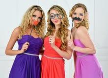 Trzy kobiety w sukni wieczorowej z maskami. zdjęcia stock