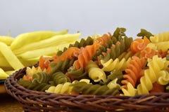 Trzy kolorów makaron w łozinowym pucharze, żółci bobowi strąki na szklanym talerzu Fotografia Royalty Free