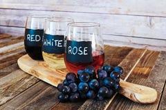 Trzy kolorów wina lot w etykietek szkłach zamyka up Zdjęcia Stock