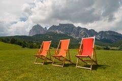 Trzy kolorowego pokładu krzesła przed piękną Tofane górą obraz stock