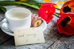 Trzy kolorowego tulipanu na drewnianym stole Filiżanka kawy, ciastka Atmosferyczny nastrój śniadanie Zdjęcie Stock