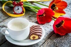 Trzy kolorowego tulipanu na drewnianym stole Filiżanka kawy, ciastka Atmosferyczny nastrój śniadanie Zdjęcie Royalty Free