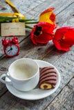 Trzy kolorowego tulipanu na drewnianym stole Filiżanka kawy, ciastka Atmosferyczny nastrój śniadanie Fotografia Stock