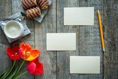Trzy kolorowego tulipanu na drewnianym stole Notepad puste miejsce dla teksta Filiżanka kawy, ciastka Obrazy Royalty Free