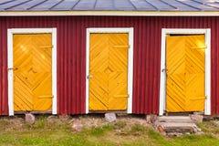 Trzy koloru żółtego zamkniętego drzwi w czerwonej wiejskiej stajni Obrazy Royalty Free